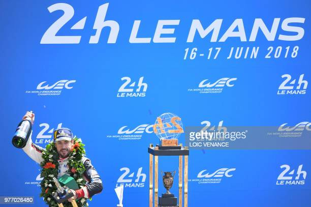 TOPSHOT Toyota TS050 Hybrid LMP1's driver Spain's Fernando Alonso celebrates on the podium after winning the 86th edition of the 24h du Mans car...