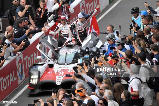 TOPSHOT Toyota TS050 Hybrid LMP1's drivers Spain's Fernando Alonso and Switzerland's Sebastien Buemi celebrate after winning the 86th edition of the...