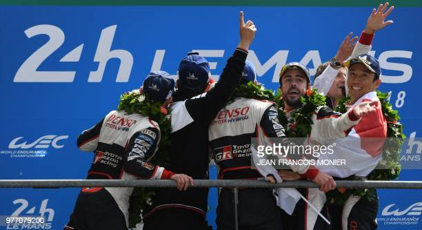 Toyota TS050 Hybrid LMP1's drivers Spain's Fernando Alonso and Japan's Kazuki Nakajima celebrate on the podium after winning the 86th Le Mans 24hours...