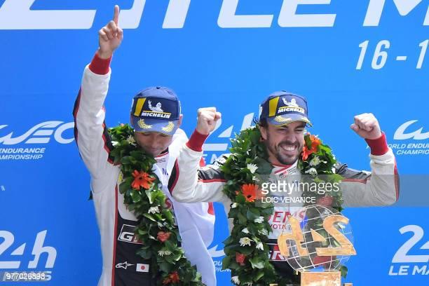 Toyota TS050 Hybrid LMP1's drivers Spain's Fernando Alonso and Toyota TS050 Hybrid LMP1 Swiss' driver Sebastien Buemi celebrates on the podium after...