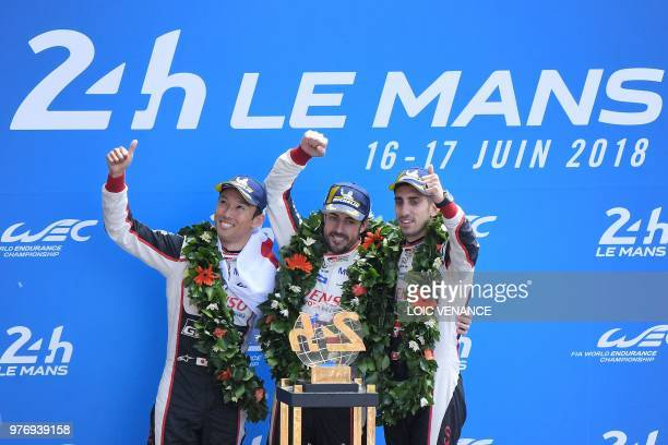 Toyota TS050 Hybrid LMP1's drivers Spain's Fernando Alonso , Japan's Kazuki Nakajima and Switzerland's Sebastien Buemi celebrate on the podium after...