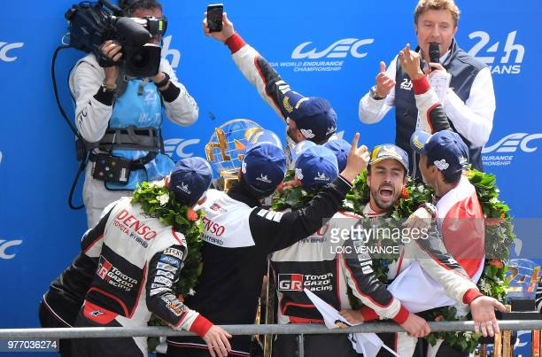 Toyota TS050 Hybrid LMP1's drivers Spain's Fernando Alonso poses for a picture with Japan's Kazuki Nakajima and Switzerland's Sebastien Buemi and...