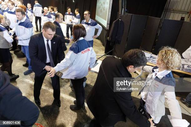 Toyota workers are checked by security before attending french President Emmanuel Macron visit at Toyota's automobile manufacturing plant in...