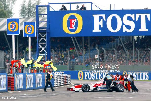 Toyota's Allan McNish is wheeled off the start/finish straight after stalling on the grid and being left behind
