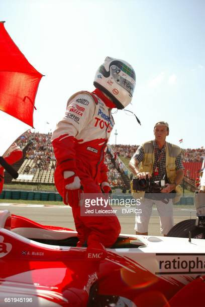Toyota's Allan McNish stands in his car on the starting grid