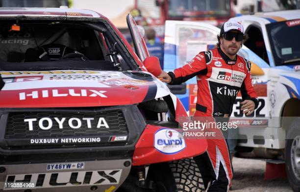 Toyota's driver Fernando Alonso of Spain leaves his damaged car during a neutralisation of the Stage 10 at the Dakar 2020 between Haradh and...