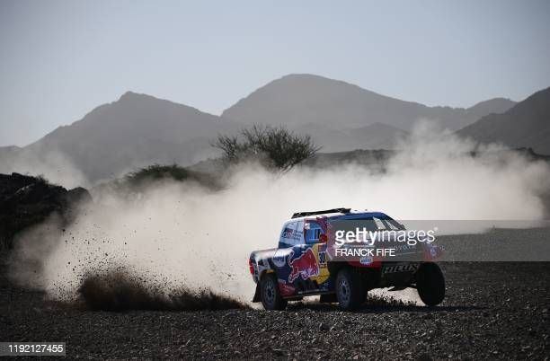 Toyota's driver Nasser Al-Attiyah of Qatar and his co-driver Mathieu Baumel of France compete during the Stage 2 of the Dakar 2020 between Al Wajh...