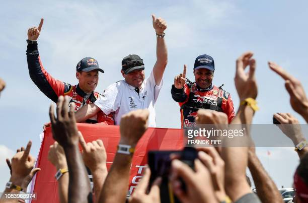 TOPSHOT Toyota's driver Nasser AlAttiyah of Qatar and his codriver Matthieu Baumel of France celebrate after winning the Dakar Rally 2019 at the end...
