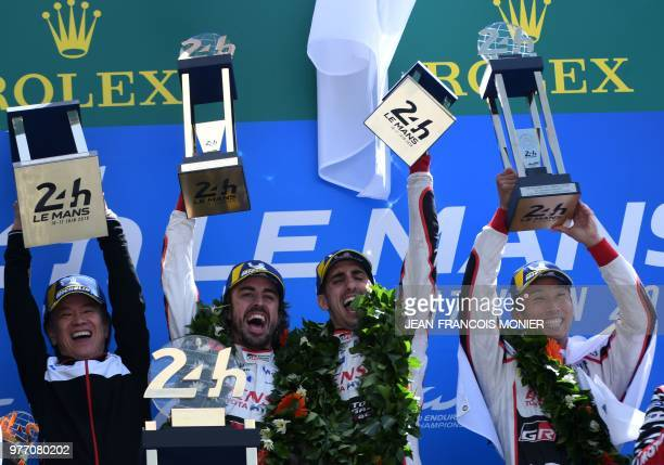 Toyota's head of motorsport Shigeki Tomoyama Spain's driver Fernando Alonso Switzerland's Sebastien Buemi and Japan's Kazuki Nakajima celebrate with...