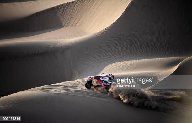 TOPSHOT Toyota's Qatari driver Nasser AlAttiyah and French codriver Mathieu Baumel ride through the dunes of Tanaca during the 2018 Dakar Rally Stage...