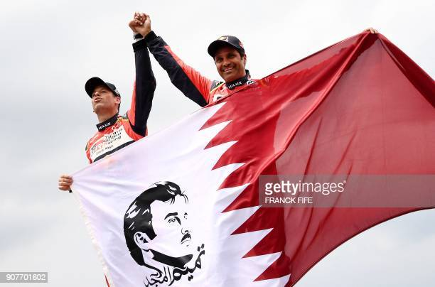 Toyota's Qatari driver Nasser AlAttiyah and his French codriver Mathieu Baumel celebrate as they hold Qatar's national flag depicting an image of...