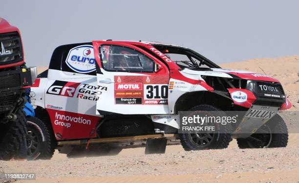 Toyota's Spanish driver Fernando Alonso and and Spanish co-driver Marc Coma drive their car after the neutralisation of the race due to strong winds...