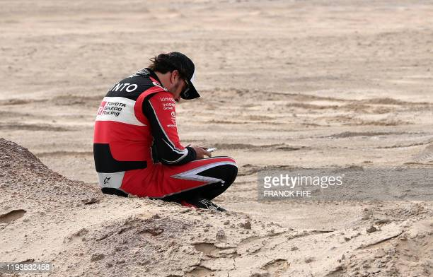 Toyota's Spanish driver Fernando Alonso reacts after the neutralisation of the race due to strong winds during the Stage 10 of the Dakar 2020 between...
