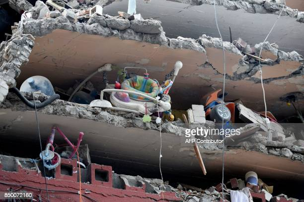 TOPSHOT Toys and a baby walker are seen in a building flattened by the strong quake that hit central Mexico on the eve taken on September 20 2017 as...
