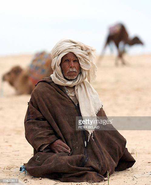 Picture taken 23 December 2006 shows Tunisian man sitting next to his camels in Nafta near Tozeur on the eve of the opening of the Sahara...