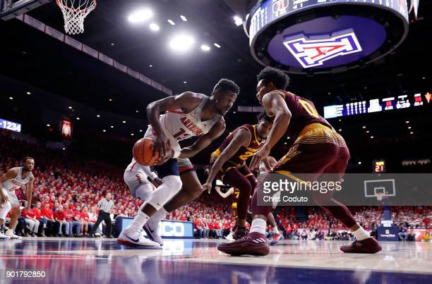 Tra Holder of the Arizona State Sun Devils and Deandre Ayton of the Arizona Wildcats fight for a loose ball during the first half of the college...