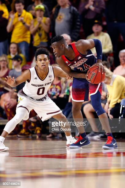 Tra Holder of the Arizona State Sun Devils defends Emmanuel Akot of the Arizona Wildcats during the second half of the college basketball game at...