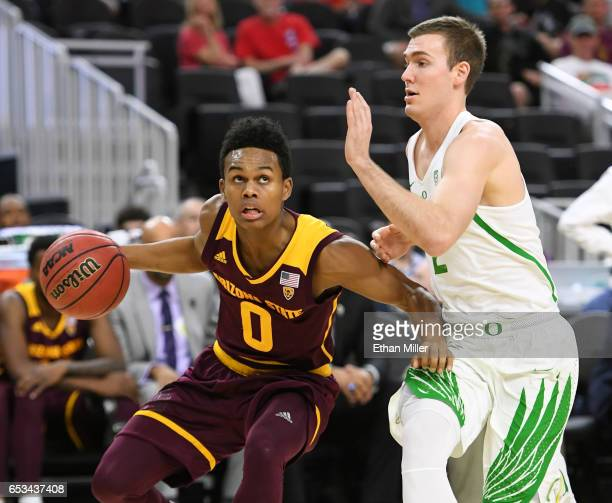 Tra Holder of the Arizona State Sun Devils drives against Casey Benson of the Oregon Ducks during a quarterfinal game of the Pac12 Basketball...