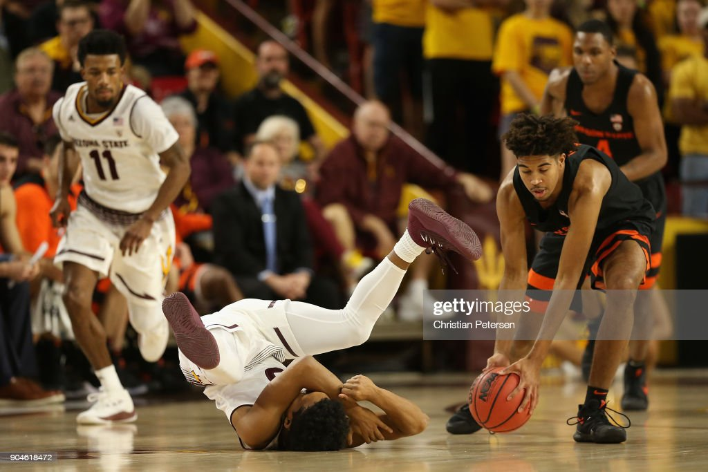 Tra Holder #0 of the Arizona State Sun Devils falls to the court with an injury as Ethan Thompson #5 of the Oregon State Beavers controls the ball during the first half of the college basketball game at Wells Fargo Arena on January 13, 2018 in Tempe, Arizona.