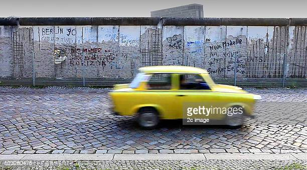 A Trabant passes the Berlin Wall on Prinz albrectstrasse Berlin Germany