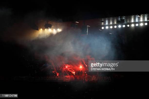 TOPSHOT Trabzonspor's supporters hold red flares and flags during the UEFA Europa League Group D football match between FC Basel 1893 and Trabzonspor...