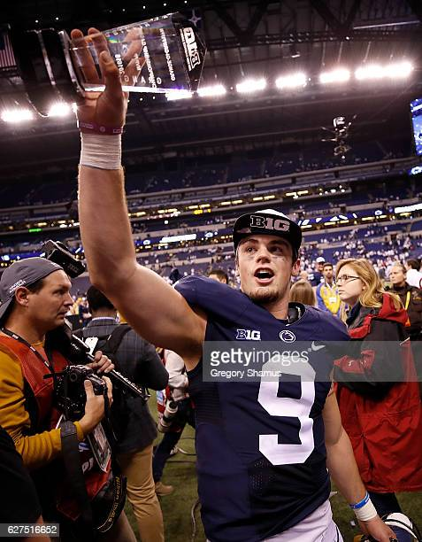 Trace McSorley of the Penn State Nittany Lions holds up the Most Valuable Player trophy as he walks off the field after the Big Ten Championship game...