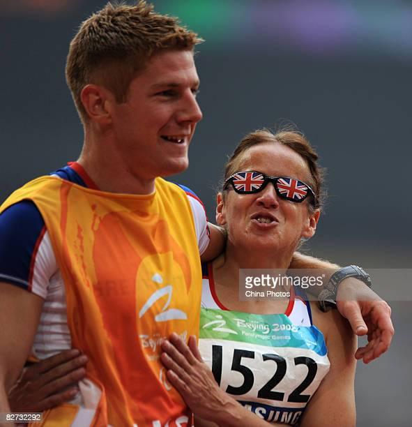 Tracey Hinton of Geat Britain holds with her guide after the Women's 100metres-T11 final Athletics event at the National Stadium during day three of...