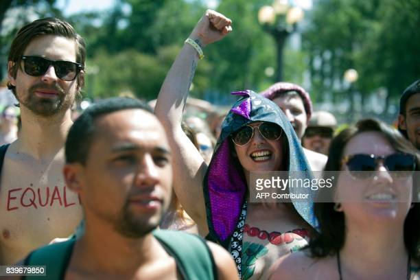 Tracey Valentine raises her fist and cheers at the beginning of the 2017 GoTopless Day Parade on August 26 2017 in Denver Colorado Founded in 2007 by...