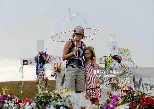 Traci Gillespie and her daughter Avery Gillespie visit a memorial setup across the street from the Century 16 movie theatre on July 27 2012 in Aurora...