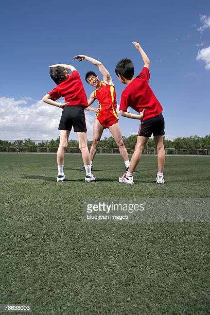 a track and field athlete is guiding two kids to do exercises. - teacher bending over stock photos and pictures