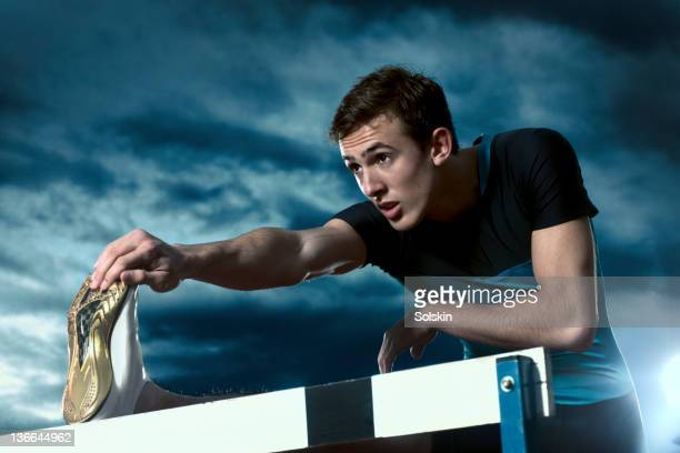 track and field athlete warming up on hurdle