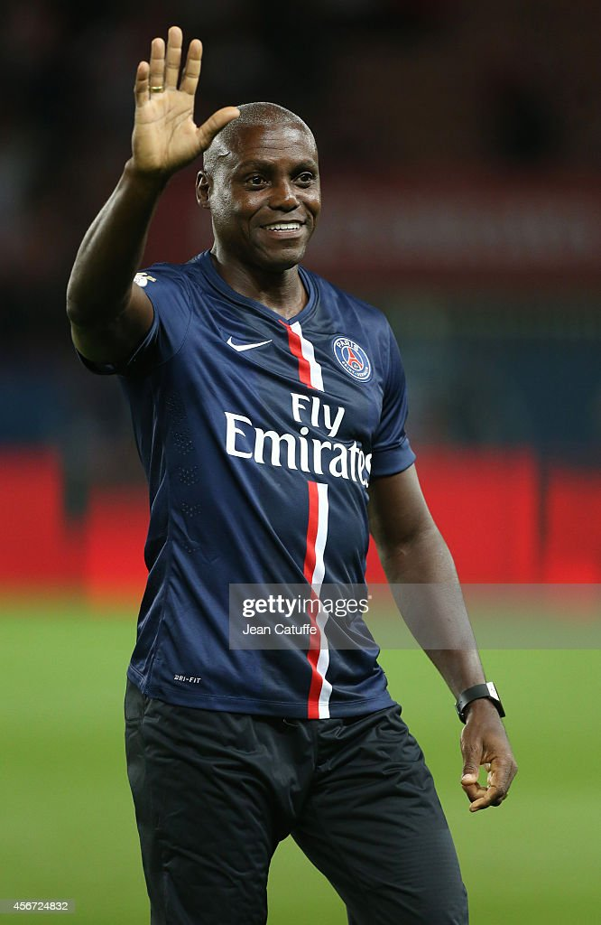 Track and field legend Carl Lewis kicks off the French Ligue 1 match between Paris Saint-Germain FC and AS Monaco at Parc des Princes stadium on October 5, 2014 in Paris, France.