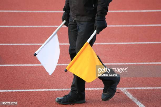 track and field official holding a yellow flag for violations and a white flag for fair call in races - judge sports official stock pictures, royalty-free photos & images