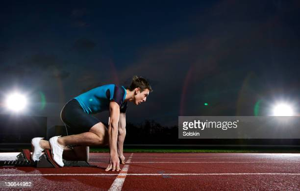 track and field sprinter getting ready in blocks