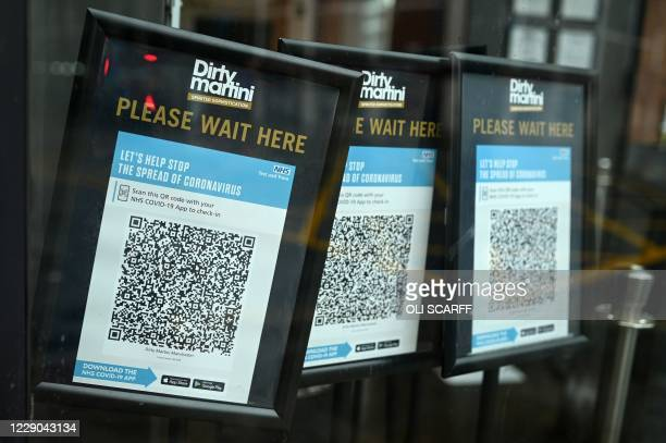 Track and trace QR codes are displayed outside a pub, in Manchester, north west England on October 13 as the number of cases of the novel coronavirus...