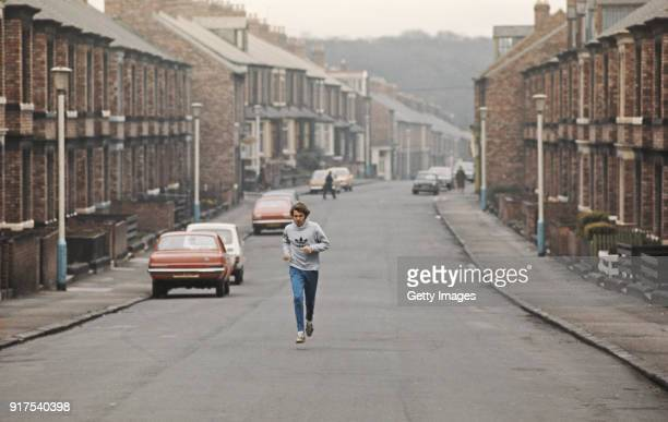 Track Athlete Brendan Foster pictured running through a terraced street during a training run circa 1977 in Gateshead England