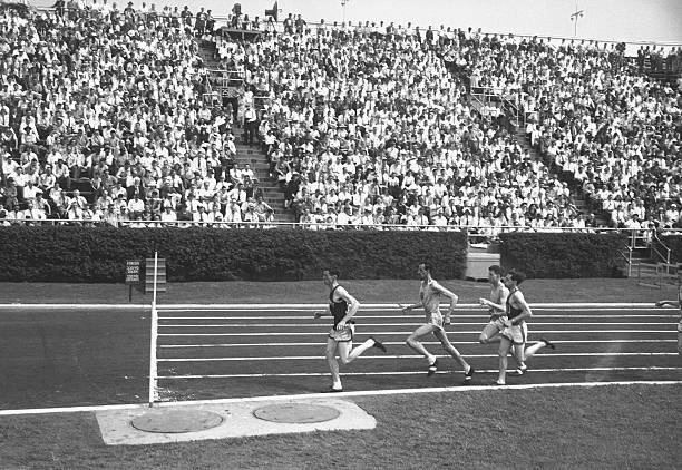 Track athletes running on track, (B&W), elevated view