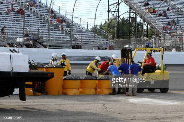 Track crews fix the entrance to pit lane after Jeremy Clements hits the barrels during the Lakes Region 200 Xfinity Series race on July 21 at New...