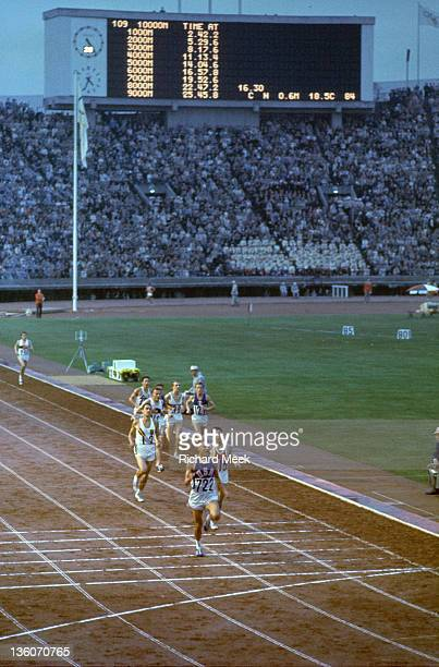 1964 Summer Olympics USA Billy Mills approaching finish line vs Australia Ron Clarke and Tunisia Mohamed Gamoudi during Men's 10000M Final at...