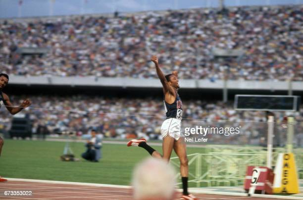 Summer Olympics: USA Tommie Smith victorious, with arm raised at the finish line, winning Men's 200M Final at Estadio Olimpico. Mexico City, Mexico...