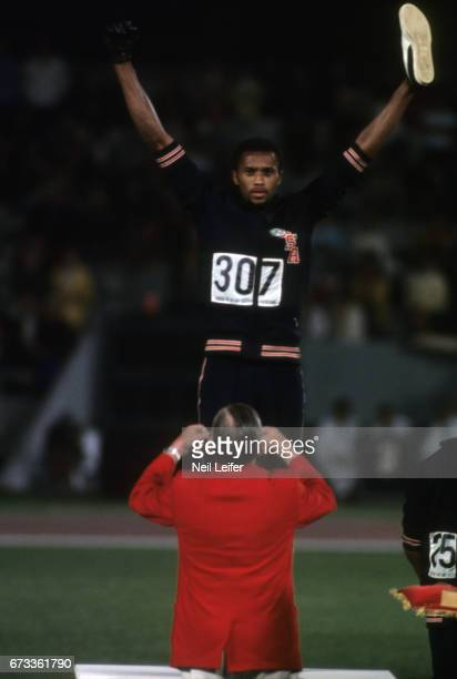 Summer Olympics: USA Tommie Smith with arms raised at medal stand presentation for the Men's 200M at Estadio Olimpico. Tommie Smith and John Carlos...