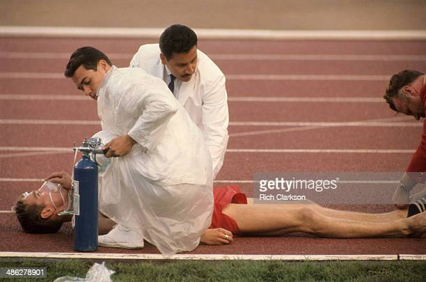 1968 Summer Olympics View of runner on track getting oxygen after collapsing during race due to altitude of Estadio Olimpico Mexico City Mexico...