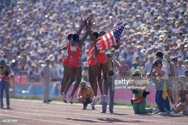 1984 Summer Olympics Team USA members Sunder Nix Ray Armstead Alonzo Roberts and Antonio McKay victorious jumping for high five on track after...