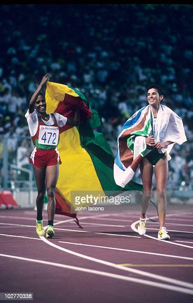 1992 Summer Olympics Ethiopia Derartu Tulu victorious with flag after winning gold medal during victory lap with South Africa Elana Meyer silver...