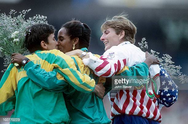 1992 Summer Olympics Rear view of South Africa Elana Meyer victorious kissing Ethiopia Derartu Tulu with USA Lynn Jennings after Women's 10000M Final...