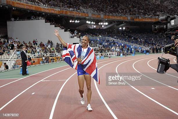 Summer Olympics: Great Britain Kelly Holmes victorious with flag after winning gold during Women's 1500M Final at Olympic Stadium. Athens, Greece...