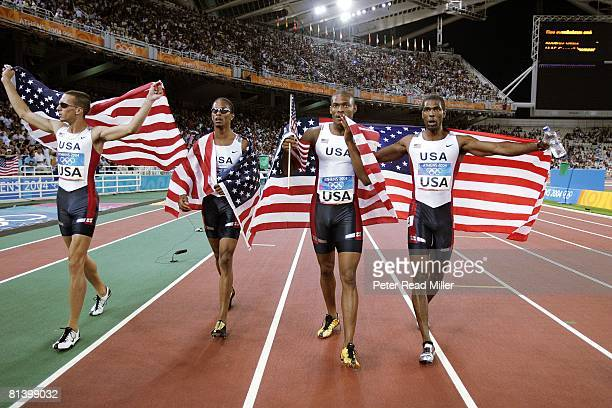 Track & Field: 2004 Summer Olympics, USA Jeremy Wariner, Darold Williamson, Otis Harris, and Derrick Brew victorious with flag after winning 4X400M...