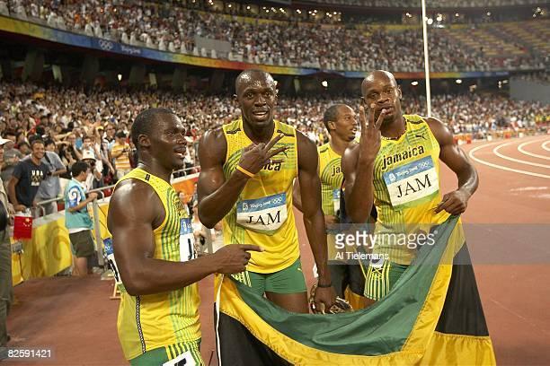2008 Summer Olympics Jamaica Nesta Carter Usain Bolt and Asafa Powell victorious with flag after winning Men's 4x100m Relay Final at National Stadium...