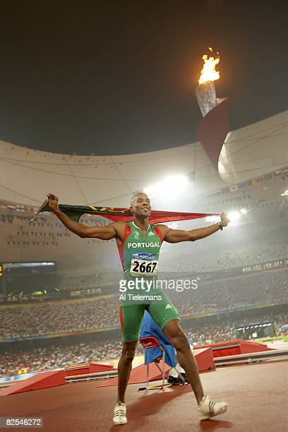 2008 Summer Olympics Portugal Nelson Evora victorious with flag after winning Men's Triple Jump gold medal at National Stadium Beijing China...
