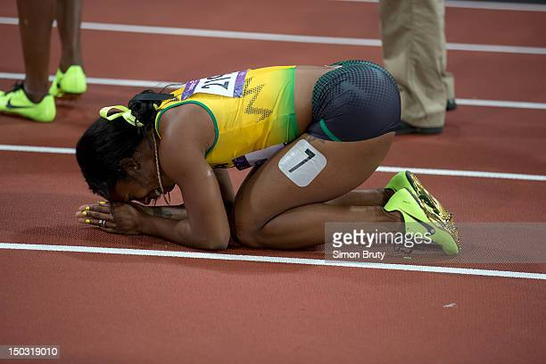 2012 Summer Olympics Jamaica ShellyAnn FraserPryce victorious kneeling on track after winning gold during Women's 100M Final at Olympic Stadium...